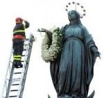 El bombero más viejo de Roma saluda a María tras dejar en su brazo una corona de flores. Francisco irá también esta tarde a dejar flores.
